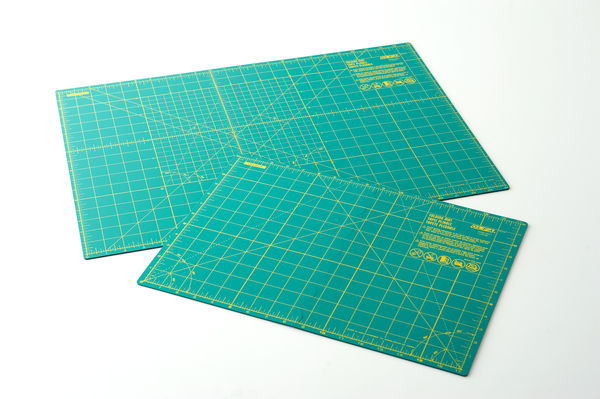 Images shows two green cutting mats of different sizes on a white background.