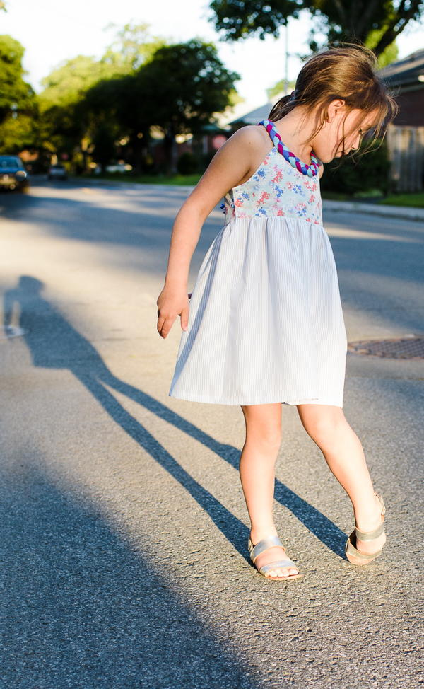 Image shows a girl standing on a street wearing the Little Lady Braided Dress.