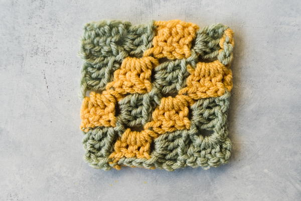 What is C2C Crochet? Image shows a corner to corner swatch in green and yellow yarn and on a marbled light gray background.