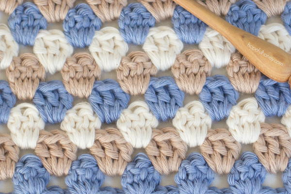 Image shows a close up of a granny stripe crochet swatch in muted brown, blue, and white. There is a wooden crochet hook at the top right.