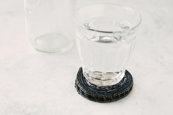 Image shows the finished rolled jean coaster sitting on a table with a glass on top. There is also a glass behind without a coaster.