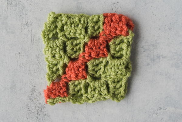 Image shows a corner to corner swatch in green and coral yarn and on a marbled light gray background.