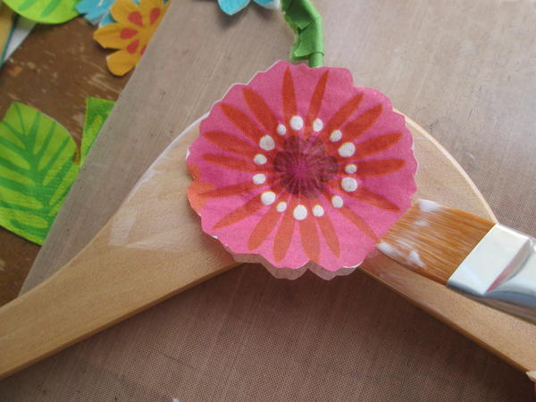 Working quickly, pick up the flower with the brush and place carefully onto the glued section of the hanger.