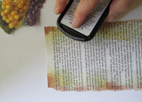 Place book page flat on work table.  Hand tear the long edges.  Using art daubers, apply ink (from light to dark) around the edges of the page; dry.