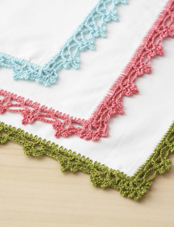 Image shows the Lace Napkin Edging design: three napkin corners with lace borders in blue, pink, and green.
