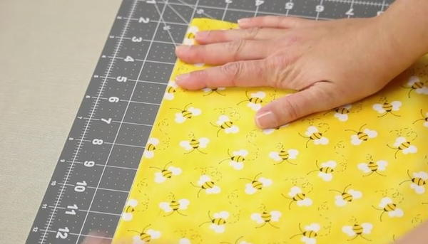 Image shows a close up of a gray cutting mat on a beige table. A hand is adjusting a yellow fabric with bees on the mat.