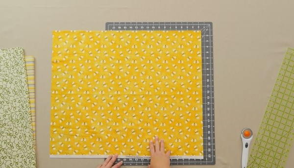 Image shows an overhead view of a gray cutting mat on a beige table. There is a stack of fabric on the left and a ruler and rotary cutter on the right. Hands are adjusting a yellow fabric with bees on the mat.