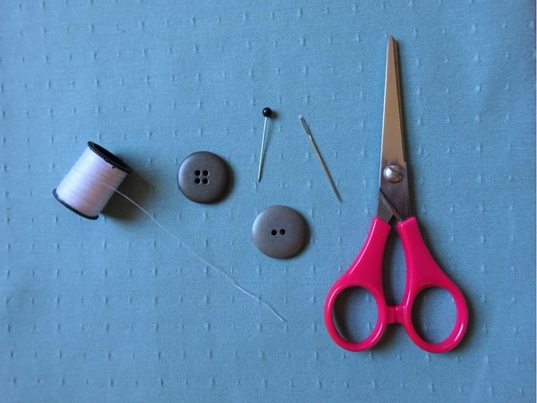 Image shows the materials needed to sew a button: thread, needle, pin, button, and scissors.