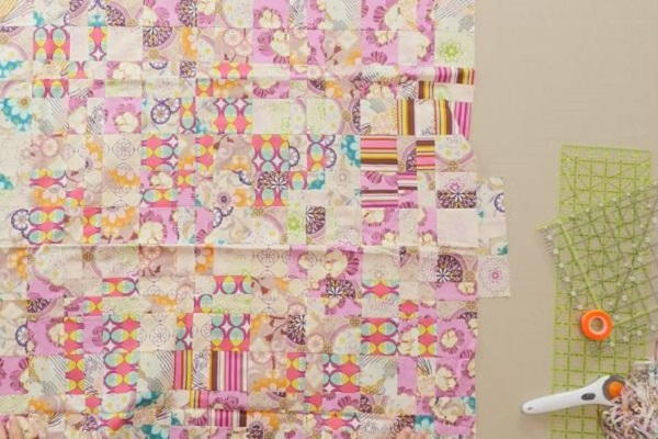 Image shows several quilt blocks sewn together on a cream background. There's a couple rulers, glow tape, and a rotary cutter off to the right side.
