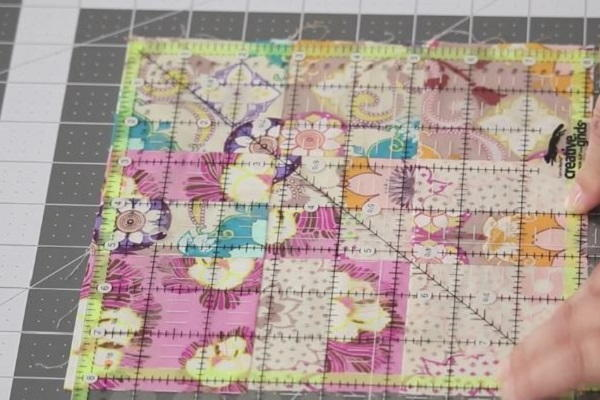 Image shows a quilt block on a cutting mat with a quilting ruler laid on top. Hands are adjusting the block and ruler to match up as needed.