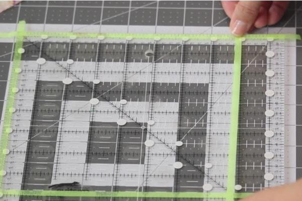 Image shows a cutting mat with a ruler laid on top. Hands are attaching glow tape to create a square.