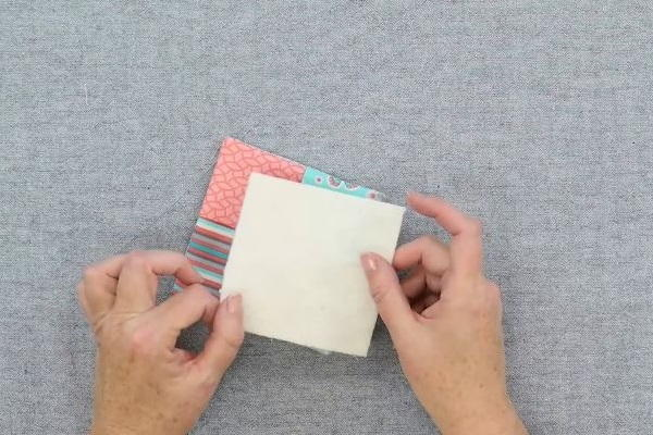 Image shows hands holding a square of cotton batting above the sewn folded fabric coaster on a gray background.