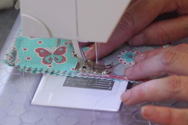 Image shows a sewing machine sewing the coaster pieces.