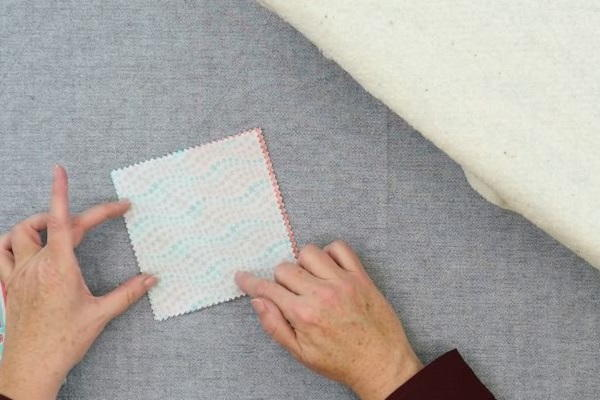 Image shows hands putting the backing square of fabric on the back of the square folded fabric coaster on a gray background.