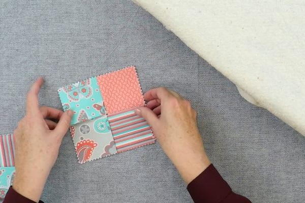 Image shows hands holding the four rectangle fabric pieces to make the square folded fabric coaster folded properly on a gray background.