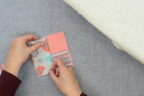 Image shows hands arranging four rectangle fabric pieces to make the square folded fabric coaster on a gray background.