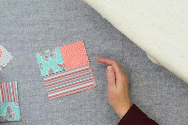 Image shows hands arranging three rectangle fabric pieces to make the square folded fabric coaster on a gray background.