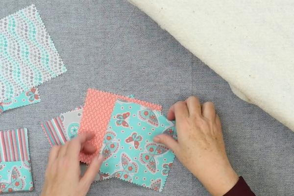 Image shows squares of fabric on a gray background. Hands are arranging them.