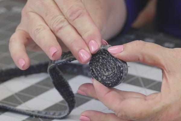 Image shows a cutting mat background with a hand holding and pressing down the rolled jean coaster in progress.