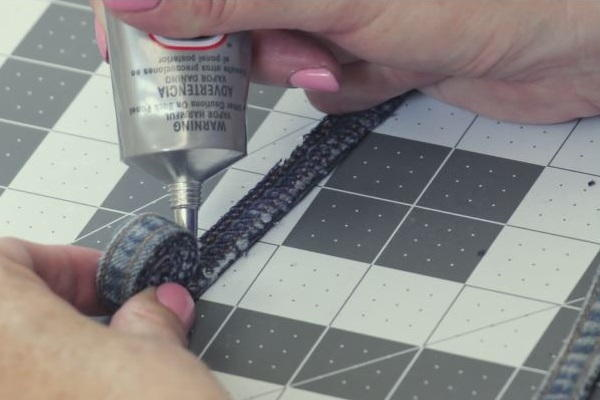 Image shows a cutting mat background with a hand gluing the rolled jean coaster on the mat.