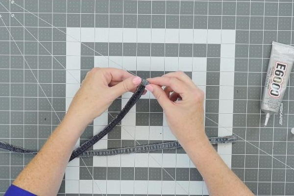 Image shows a cutting mat background with hands rolling the jean fabric strip.