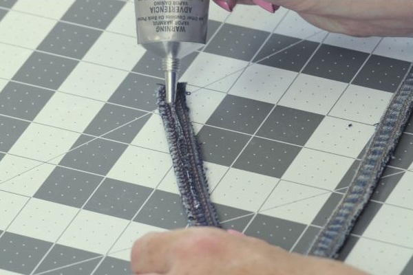 Image shows a cutting mat background with a hand gluing the jean fabric strip.