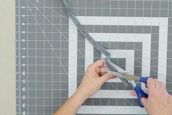 Image shows a cutting mat background with two hands cutting the seam from a pair of jeans.