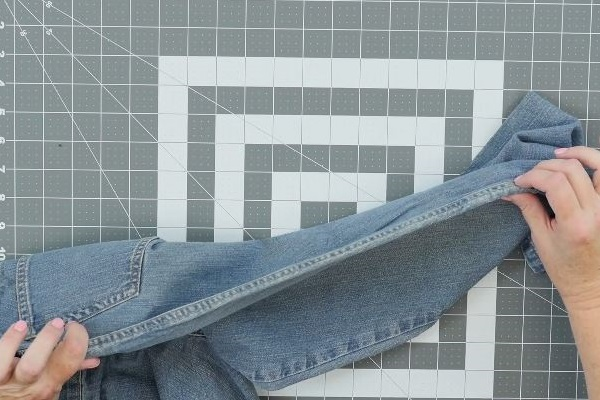 Image shows a cutting mat background with two hands holding the with the double-stitched seam side of a pair of jeans.