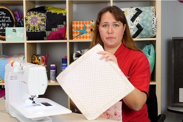 Image shows Carolina Moore holding the finished fabric swatch showing the grid design.