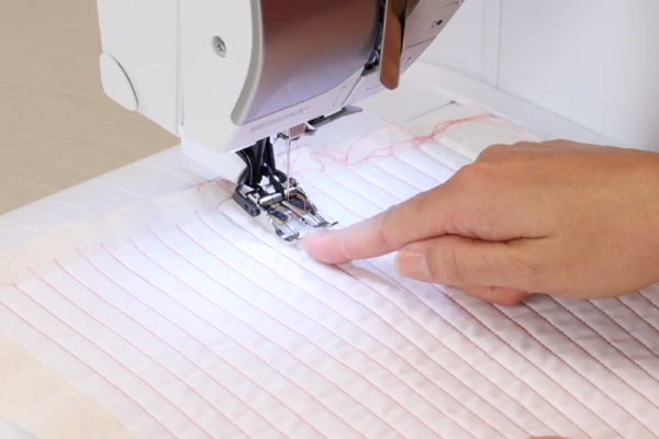Image shows a machine sewing the matchstick design.