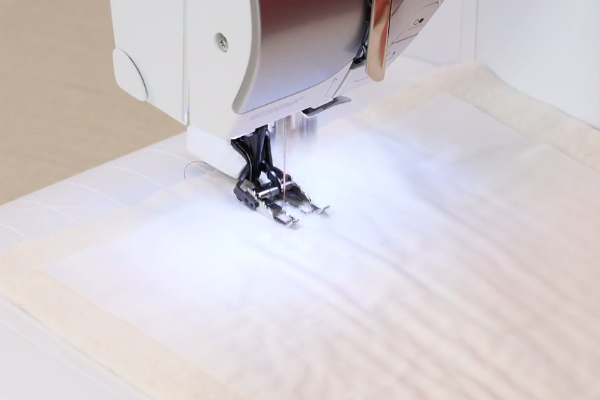Image shows a machine sewing the straight line design.