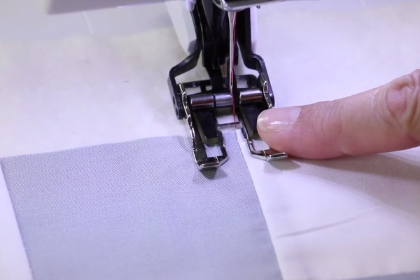 Image shows a machine sewing the stitch in a ditch design.