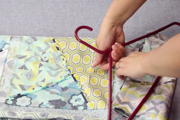 Image shows hands putting the unfinished folded quilt onto a red plastic hanger.