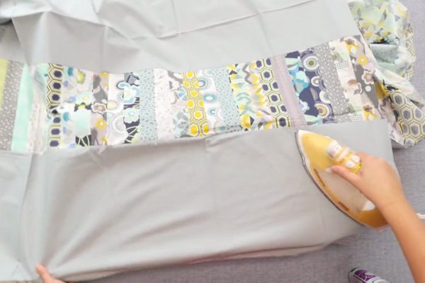 Image shows hands flattening and ironing the quilt back on an ironing board on gray surface.