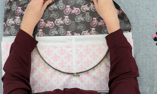 Image shows hands adjusting the outer embroidery hoop over another set of fabric pieces (the pockets).