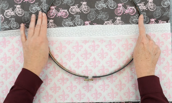 Image shows hands pushing the outer embroidery hoop over another set of fabric pieces (the pockets).
