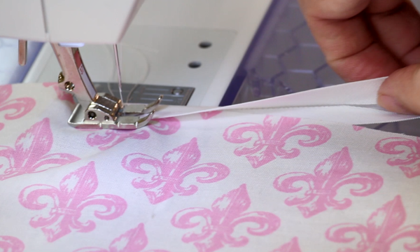 Image shows a close-up of a sewing machine sewing bias tape over the edges of white fabric with pink fleur-de-lis designs.