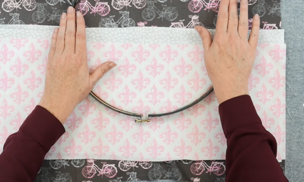 Image shows hands pushing the outer embroidery hoop over another set of fabric pieces (to be the pockets).