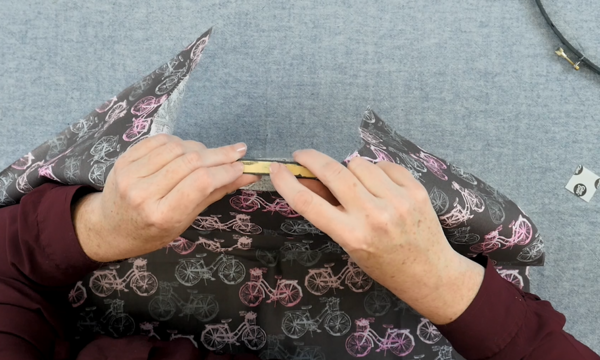 Image shows hands holding up and adjusting the embroidery hoop to hold the fabric in place.