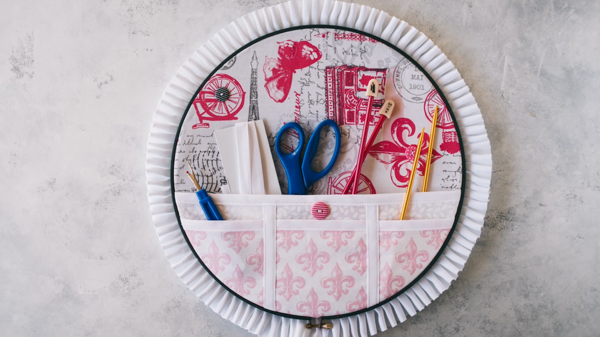 Image shows finished embroidery hoop organizer with tools inside the pockets.