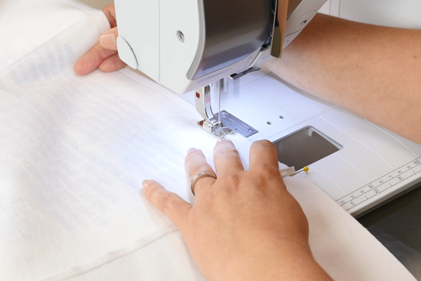 Image shows a close up of a sewing machine sewing the blocks together.