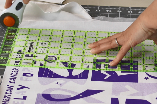 Image shows a shirt quilt block up close with a ruler over it and a rotary cutter starting to cut.
