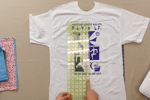 Image shows shirt on a table. Hands are using a ruler to measure the shirt design.