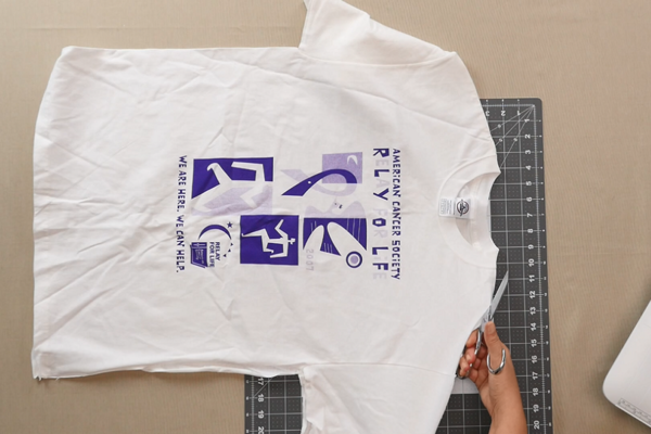 Image shows a shirt being cut.