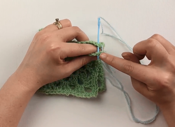 Image shows two hands whip stitching two green granny squares together with a blue yarn needle and yarn.