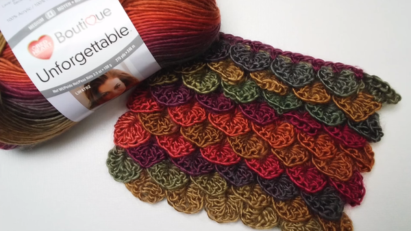Image shows a skein of yarn on the left and a crocodile stitch crochet swatch in multiple colors.