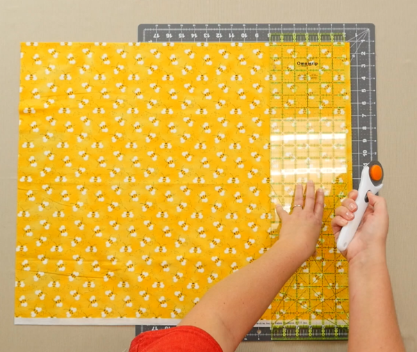 Image shows an overhead view of a gray cutting mat on a beige table. One hand is adjusting a clear quilting ruler over the yellow fabric with bees on the mat. The other hand is holding a rotary cutter.