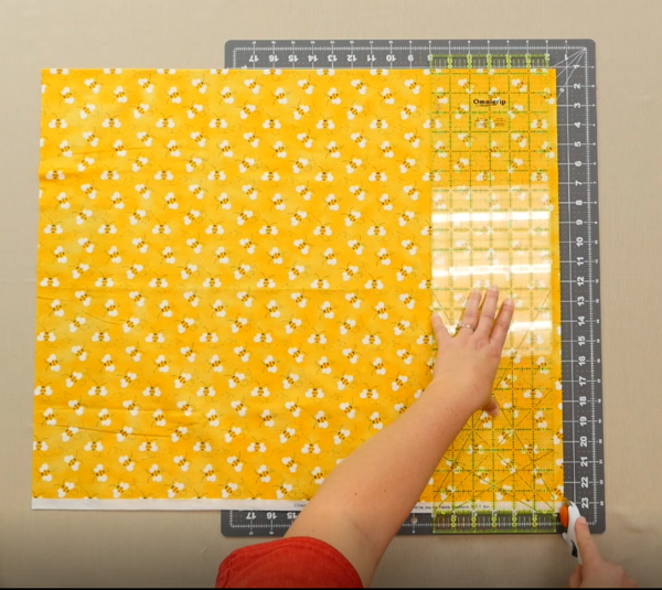Image shows an overhead view of a gray cutting mat on a beige table. One hand is holding down a clear quilting ruler over the yellow fabric with bees on the mat. The other hand is holding the rotary cutter down at the bottom edge of the fabric and ruler,