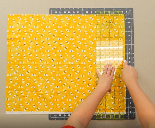 Image shows an overhead view of a gray cutting mat on a beige table. One hand is holding down a clear quilting ruler over the yellow fabric with bees on the mat. The other hand is holding the rotary cutter, cutting up about halfway to the top of the fabri