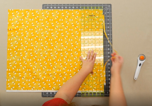 Image shows an overhead view of a gray cutting mat on a beige table. One hand is holding down a clear quilting ruler over the yellow fabric with bees on the mat. The other hand is pulling off the cut excess fabric. The rotary cutter is sitting off to the